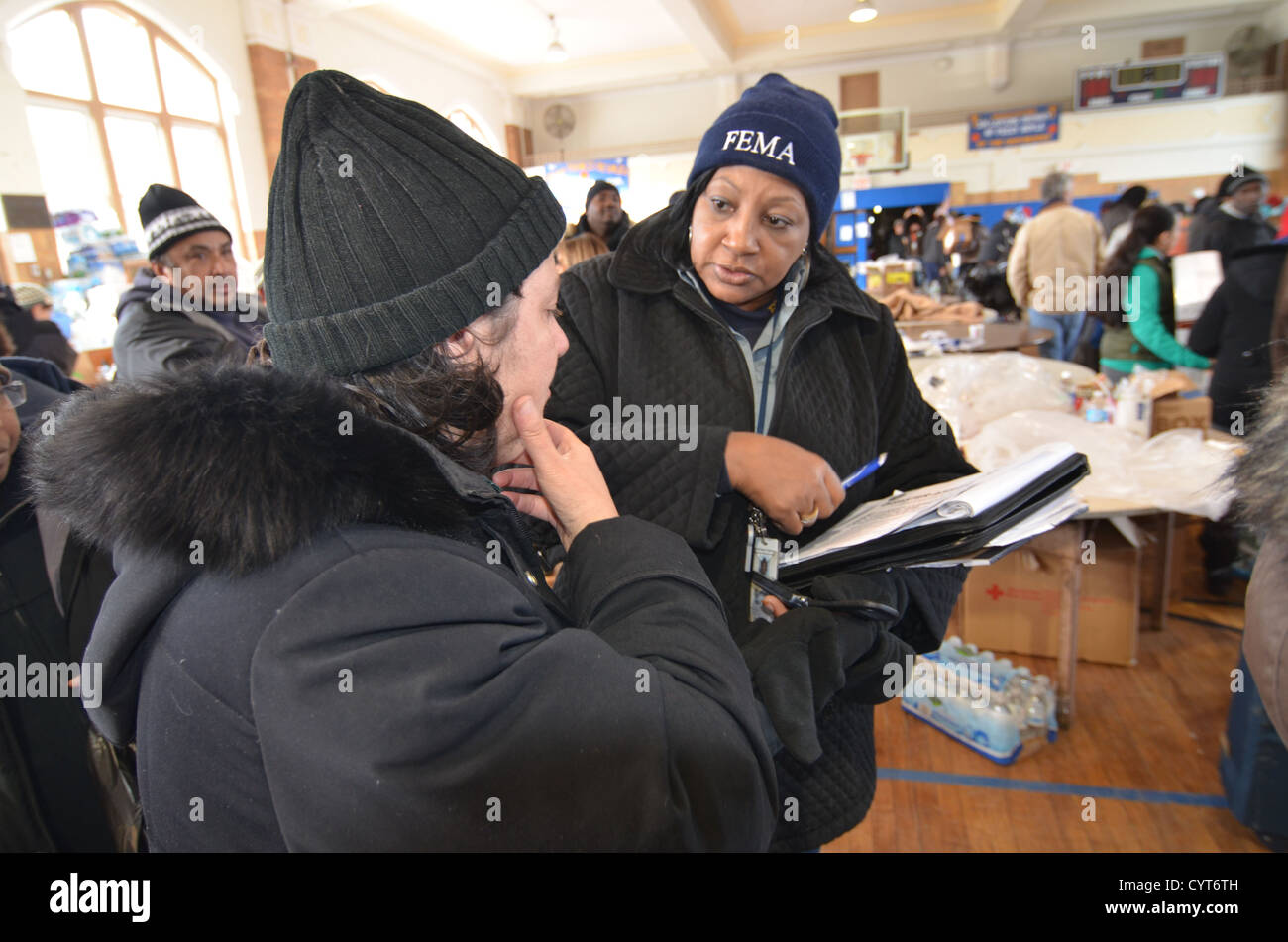 A FEMA community relations worker talks to a homeless woman in the Rockaways area near New York City who is in need - Stock Image