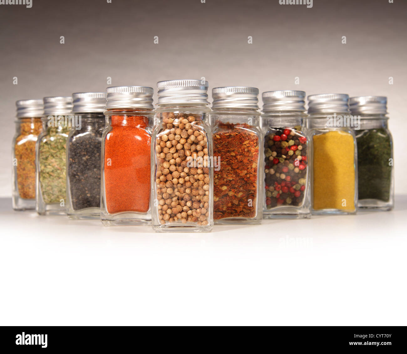 Bottles of colorful spices with grey background - Stock Image