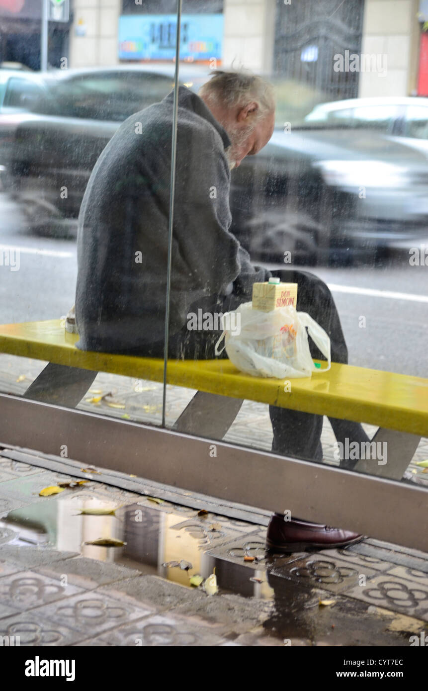 Outcast drinking cheap wine in a bus stop of Barcelona in a rainy day - Stock Image