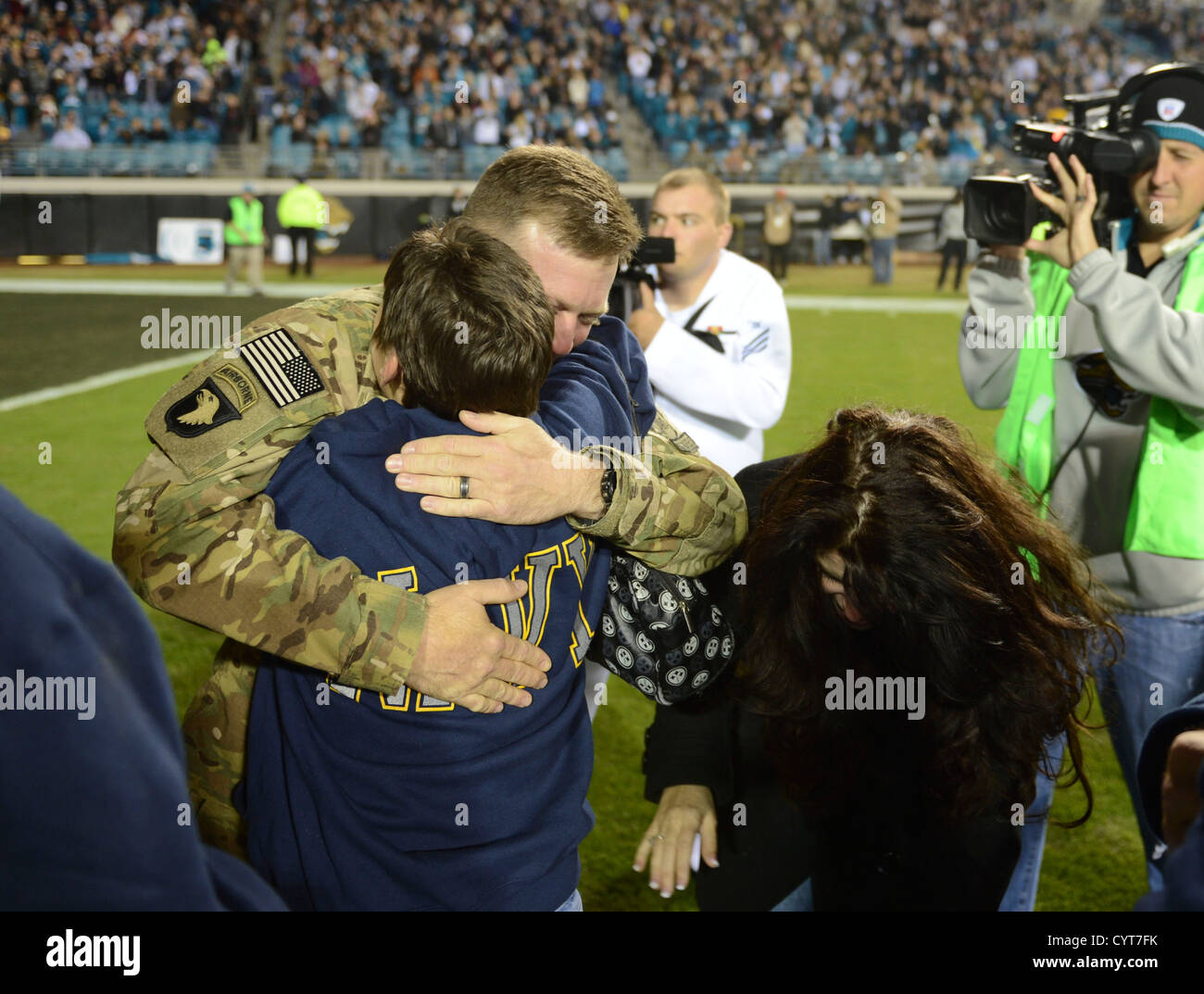 Construction mechanic first class William Cook is received by his family after surprising them at half time at EverBank - Stock Image