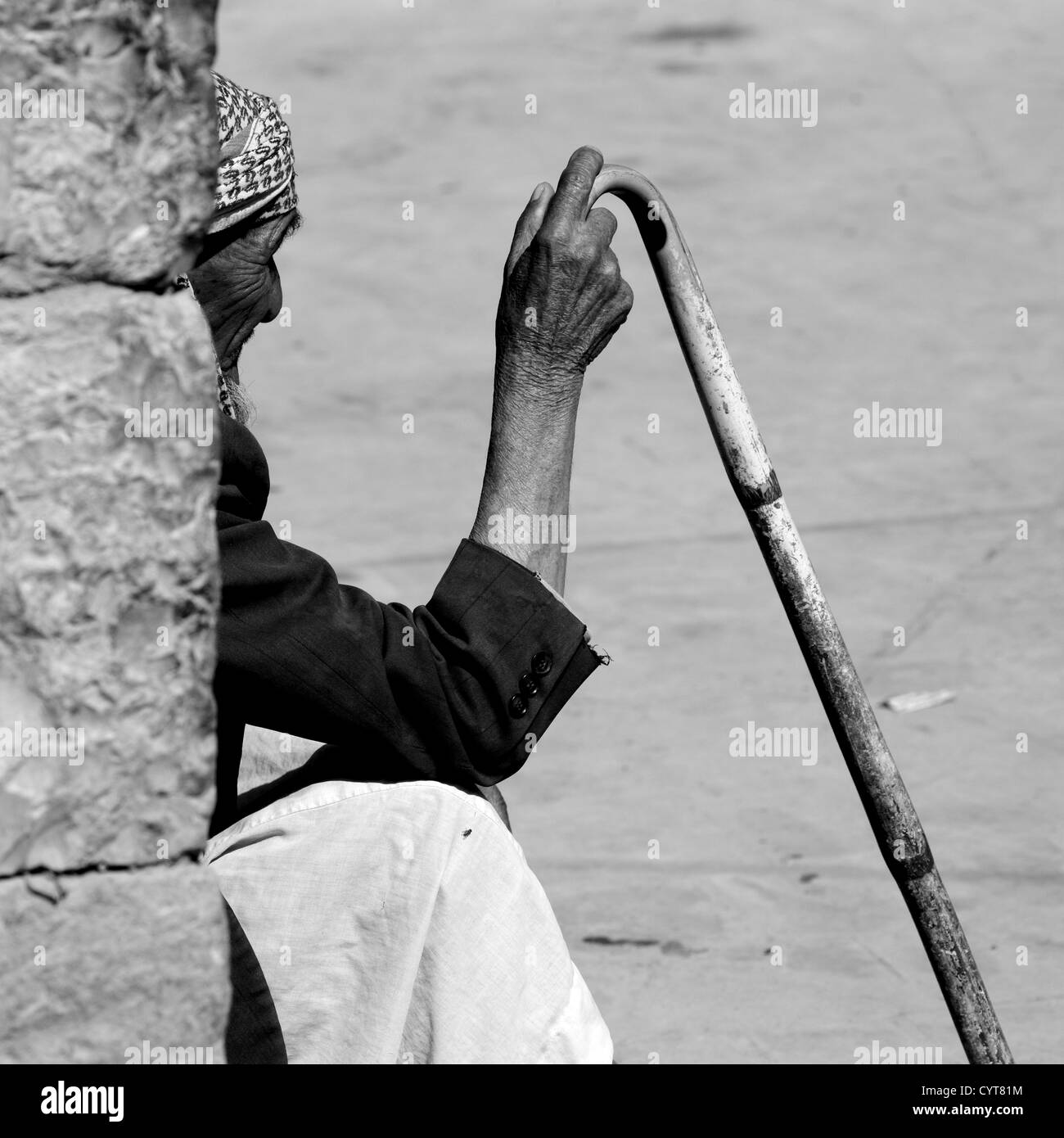 Old Man Sitting Against A Wall And Holding A Cane In Shibam, Yemen - Stock Image