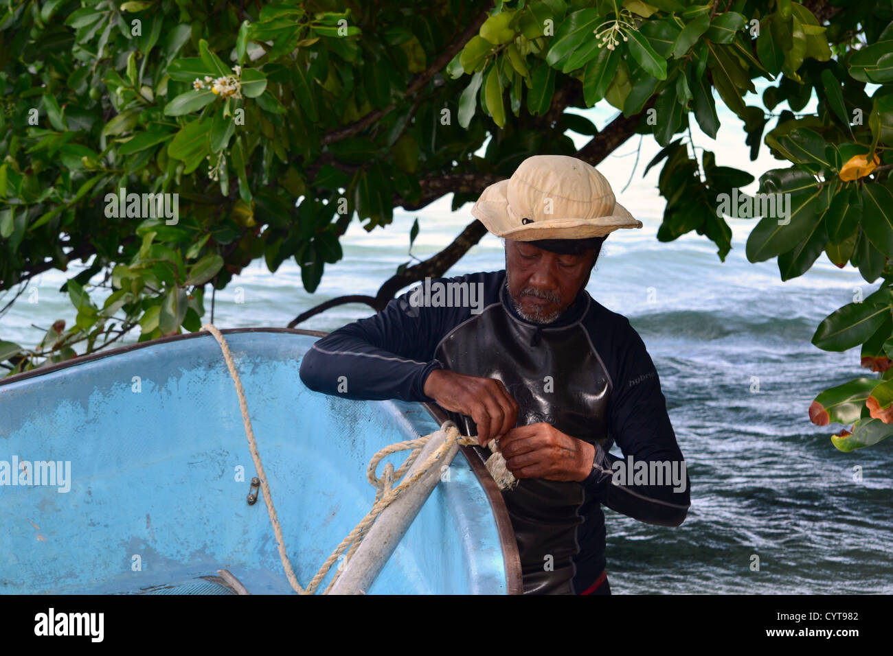 Micronesian old man ties his boat to a tree, Na Island, Madolenihmw Province, Pohnpei, Federated States of Micronesia - Stock Image