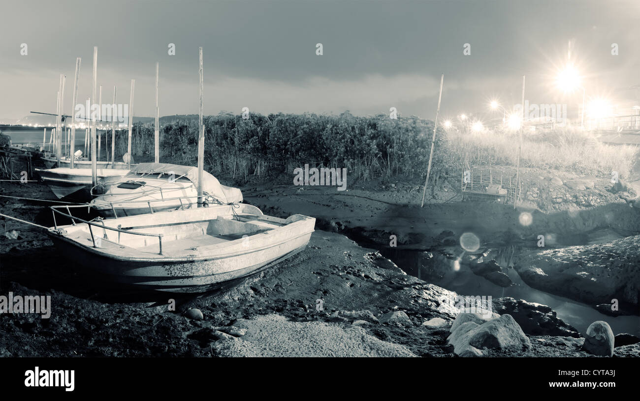 City scenery of discard boats on silt of river in night. - Stock Image