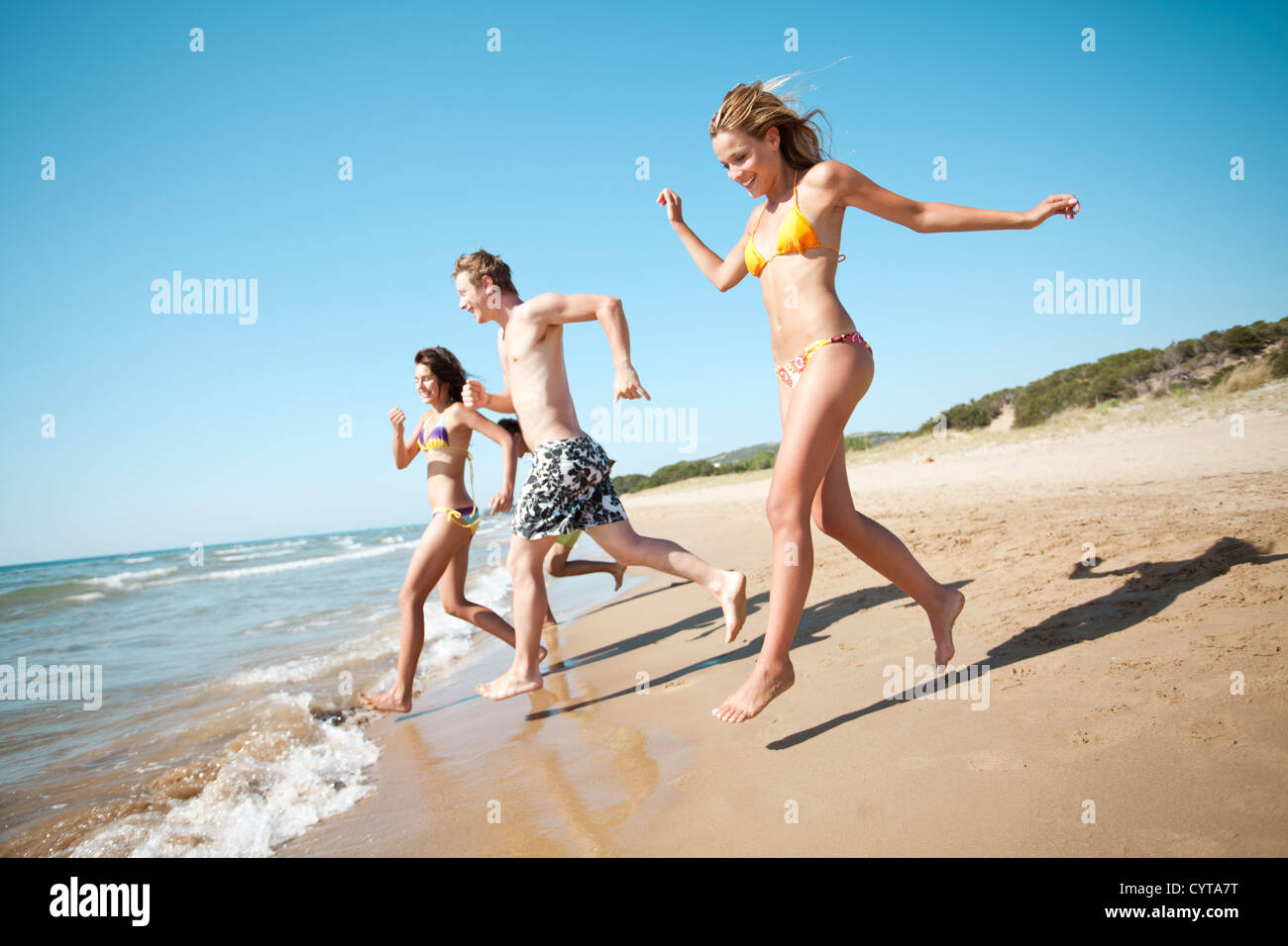 group of young people running into the sea - Stock Image
