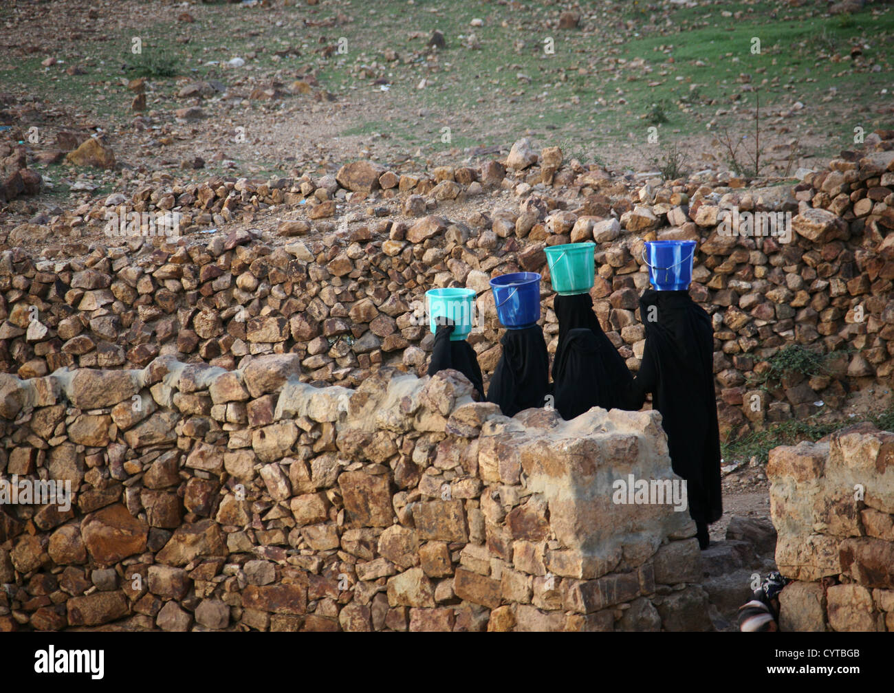 Women In Black Walking In Line With A Bucket On Their Head To Go Fetch Water, Shahara, Yemen - Stock Image