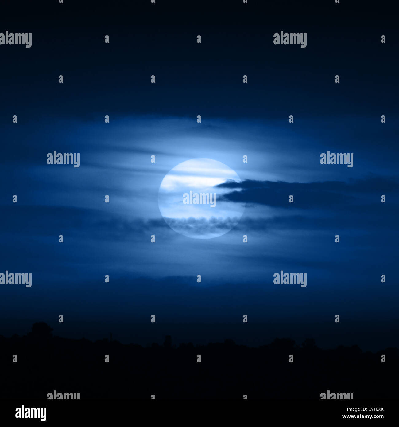 Full moon in blue clouds at night Stock Photo