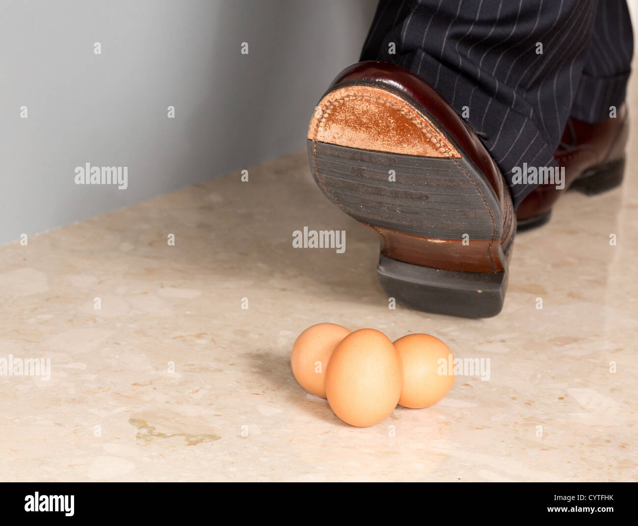 Male brown leather shoe in suit pants about to tread on three brown eggs - Stock Image