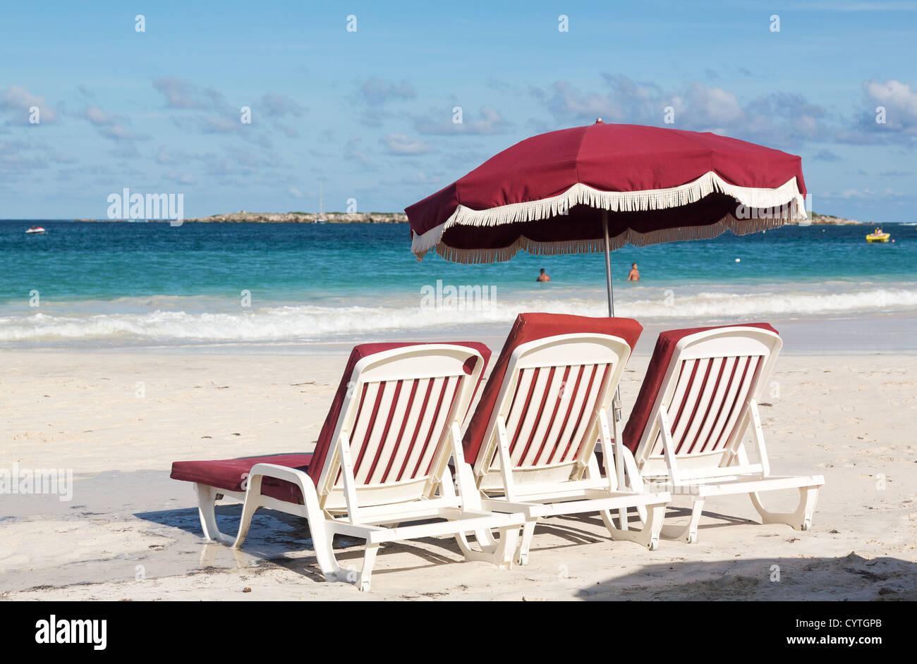 Three beach loungers and umbrella on Orient Beach on Sint Maarten /  St Martin, Caribbean - Stock Image
