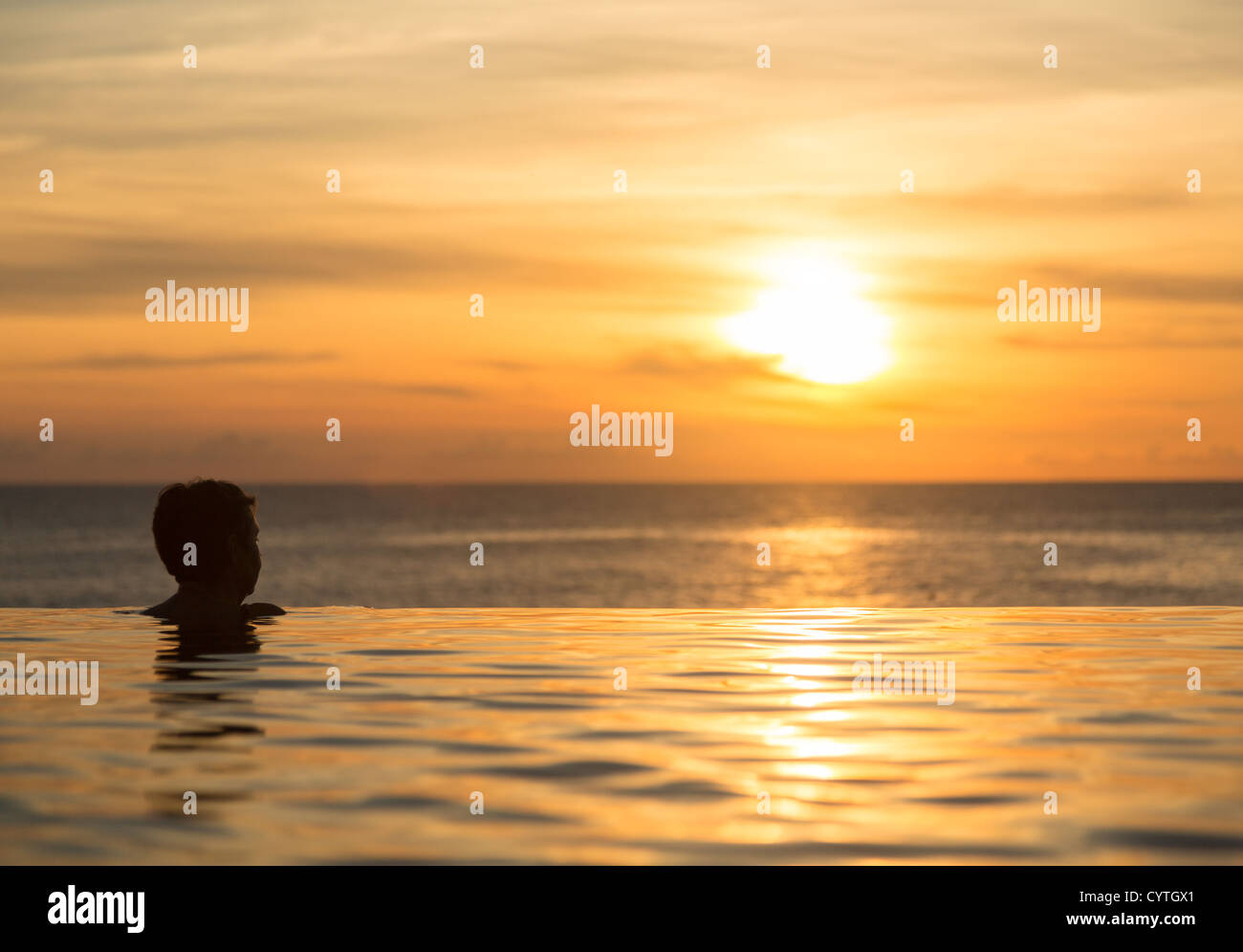 Silhouette of person head at the edge of a beautiful infinity pool overlooking sunset ocean - Stock Image