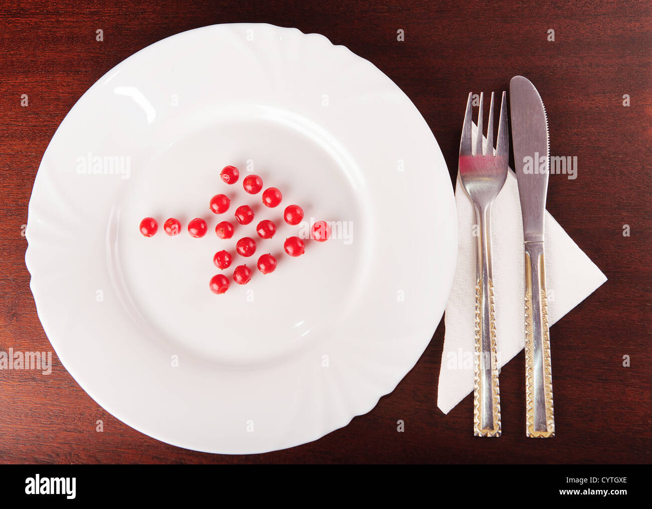 Arrow from red balls on white shows the direction to silverware Stock Photo