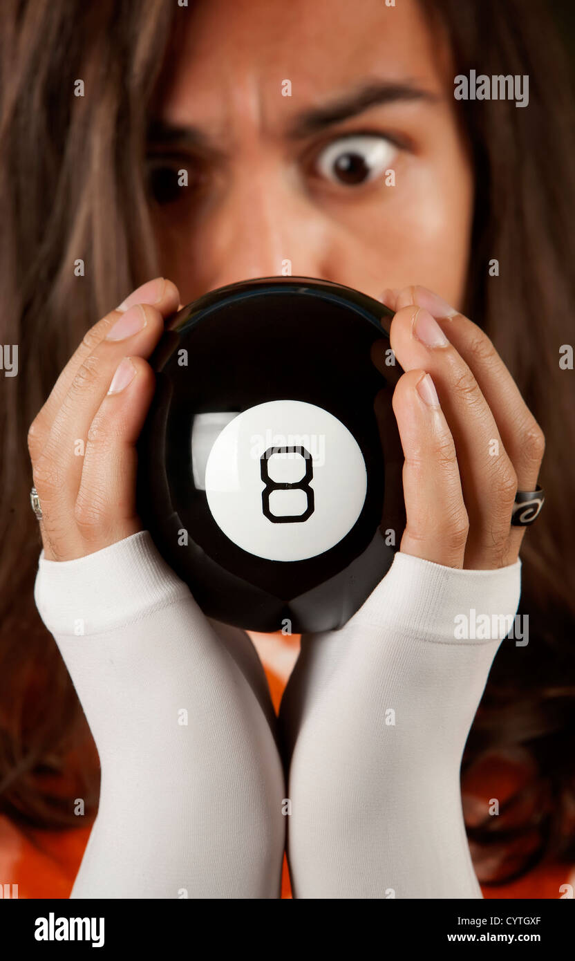 Man looking at the prediction on a magic toy ball - Stock Image