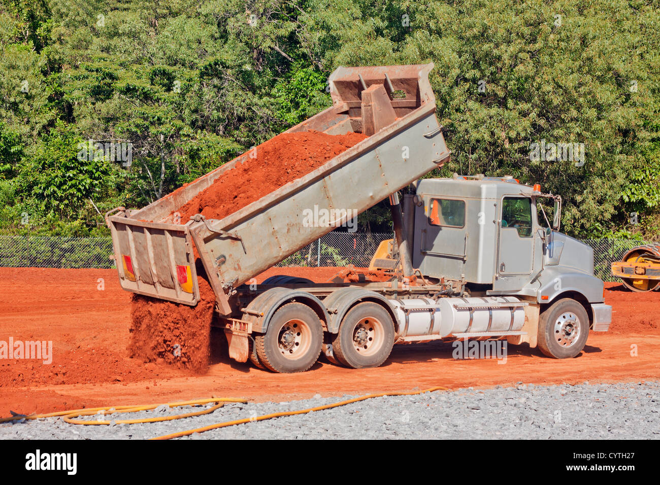 A tip truck is dumping red dirt or soil at a construction site - Stock Image