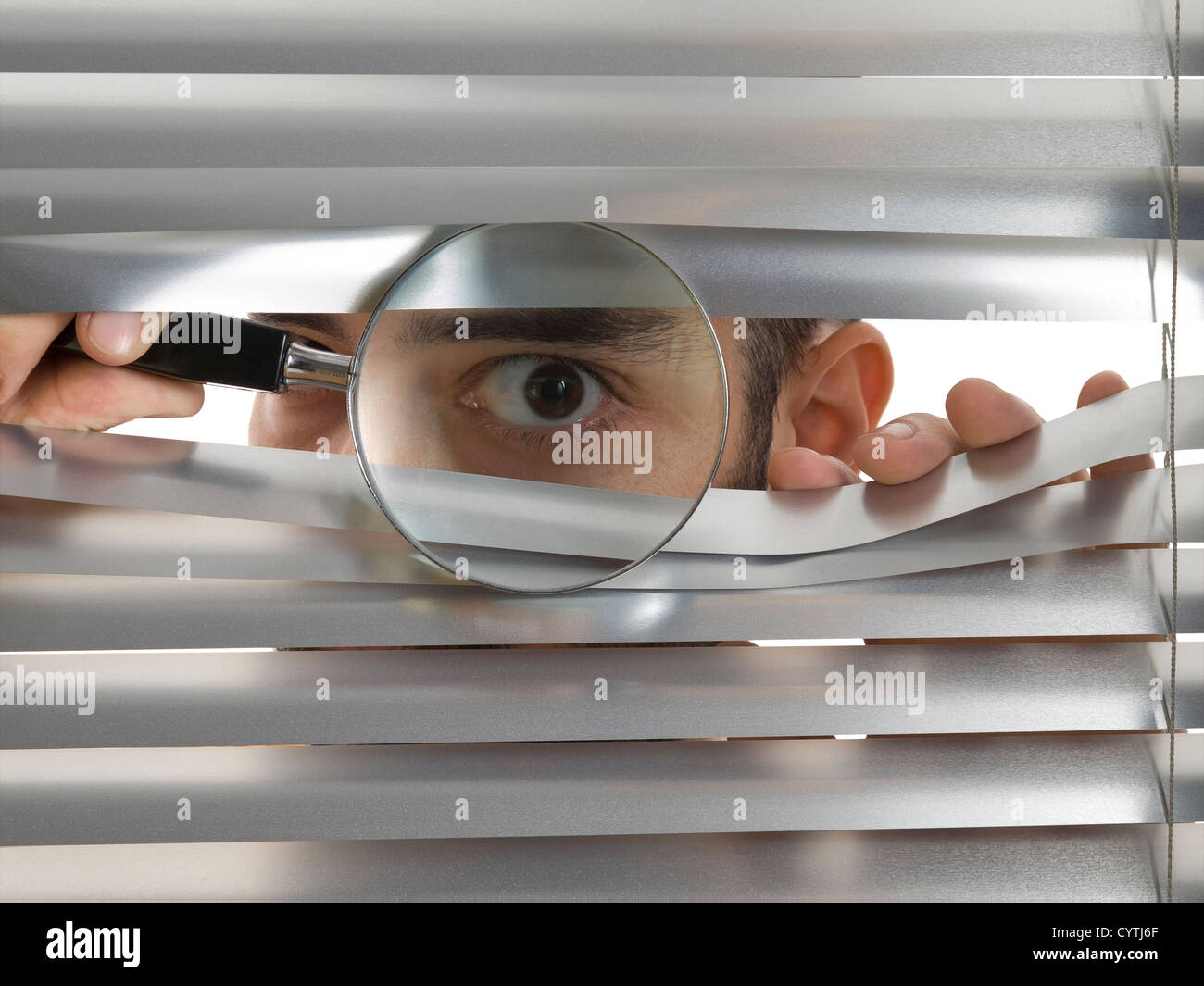 A man is peeping through the blinds with a magnifying glass. - Stock Image