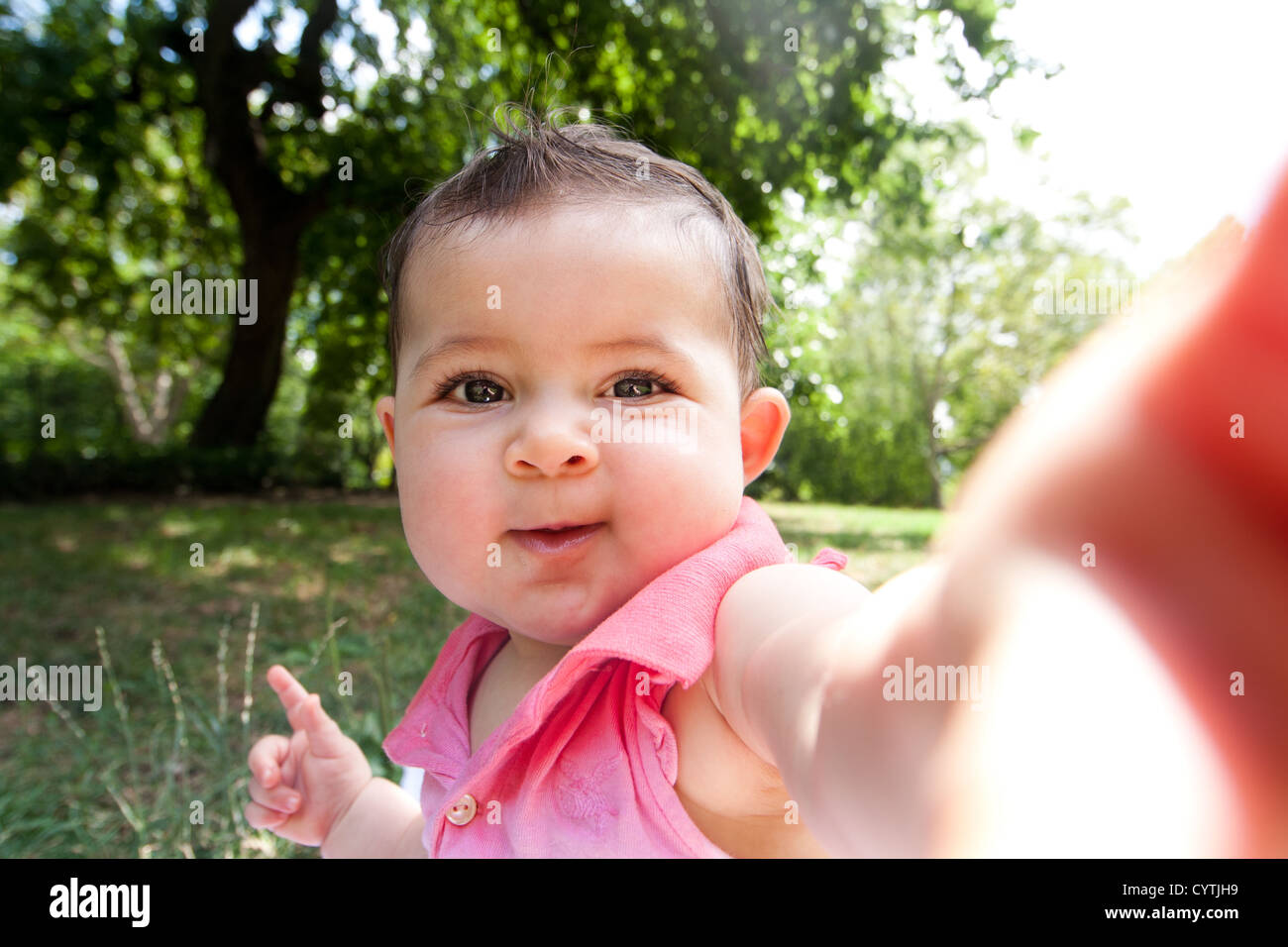 Cute funny happy baby infant sticking arm out as if she's taking self portrait photo in a park. - Stock Image