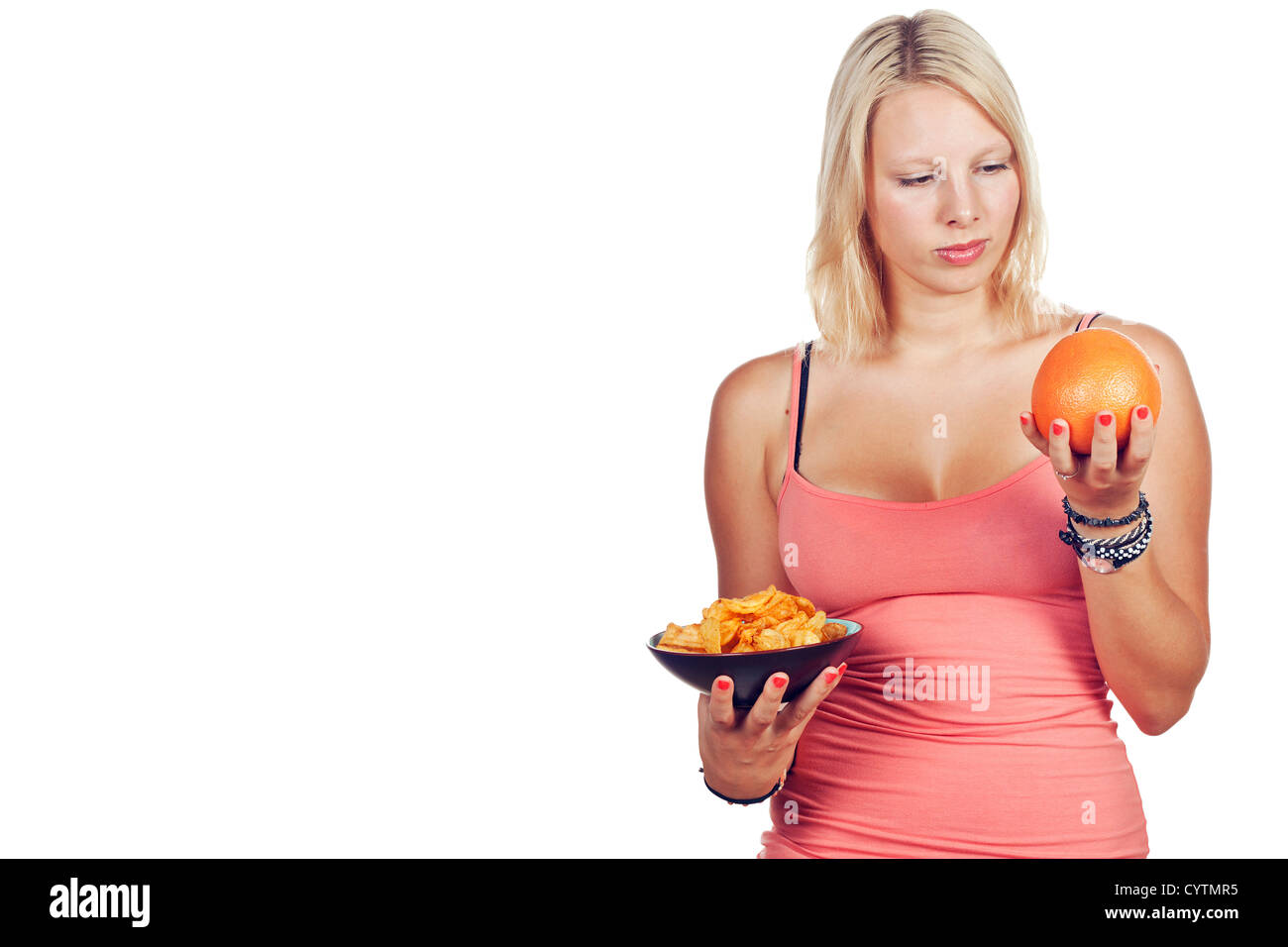 Attractive girl deciding to eat junk food or fruit. Isolated over white. - Stock Image