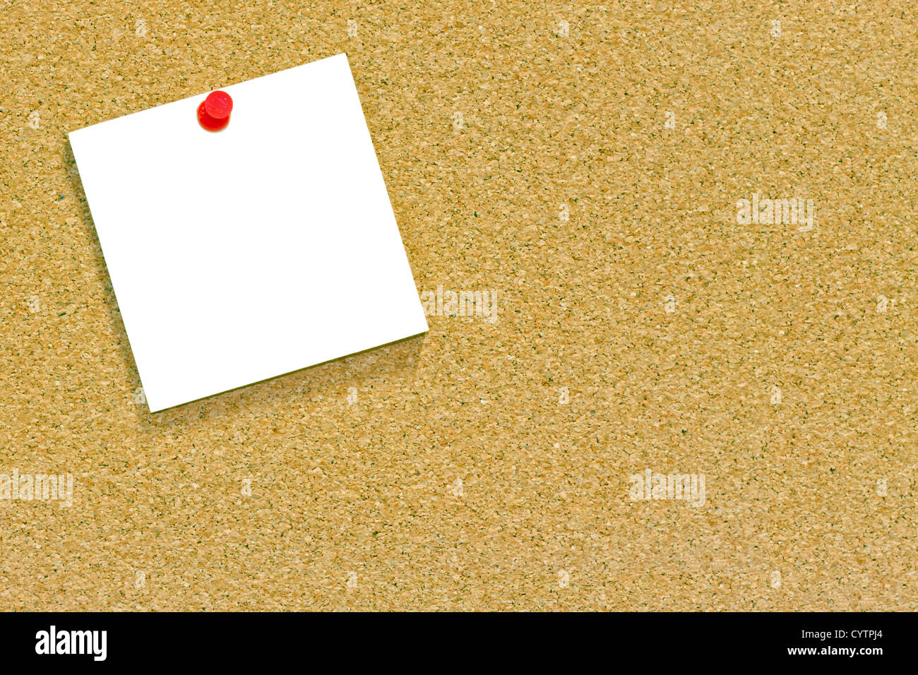 A blank memo or sticky note tacked to a cork notice board with copyspace. - Stock Image