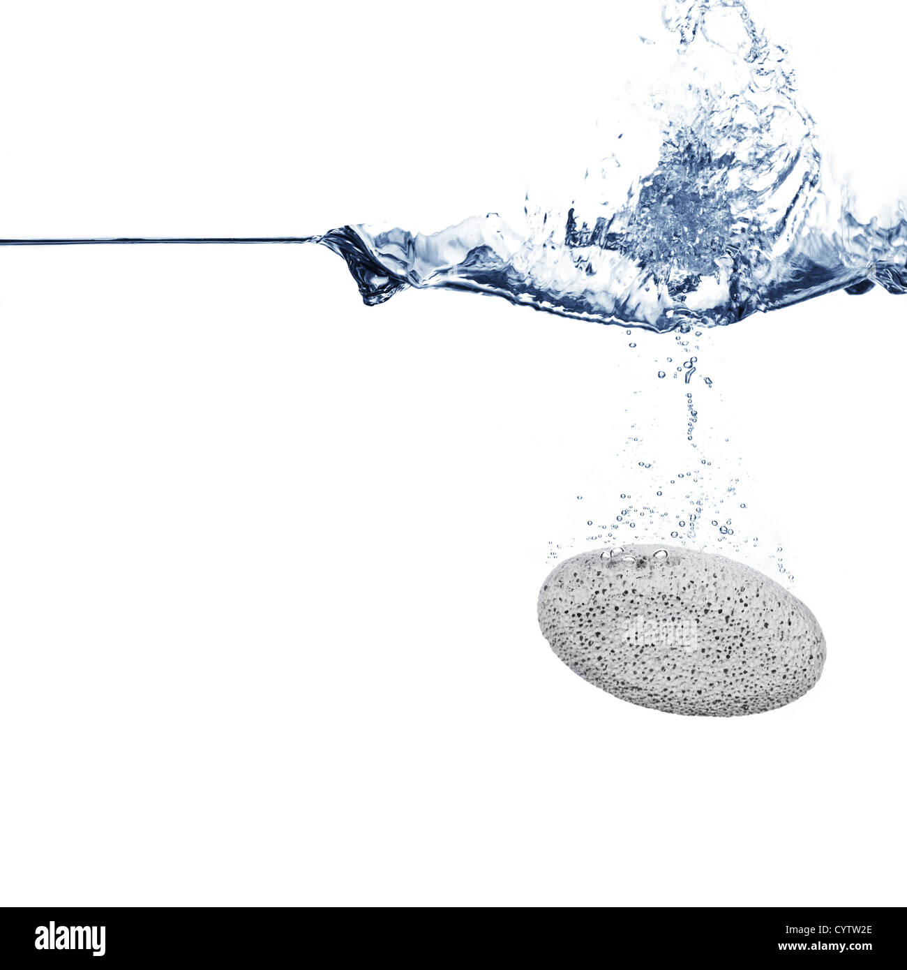 Pumice stone falling into crisp clear water. - Stock Image