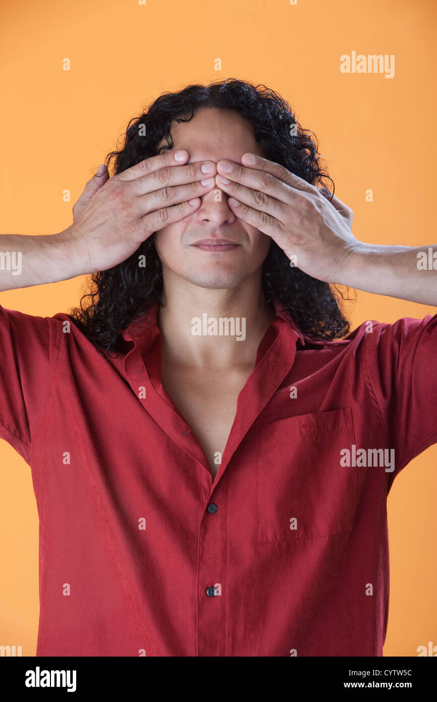 Handsome curly haired man covering his eyes with his hands - Stock Image
