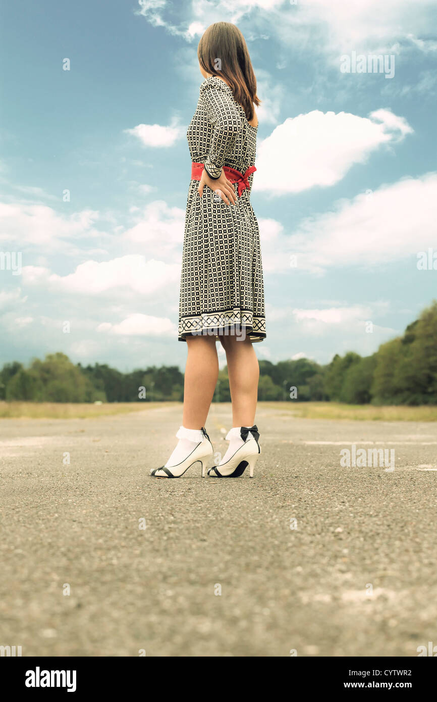 a woman in a black and white dress is standing on a street - Stock Image