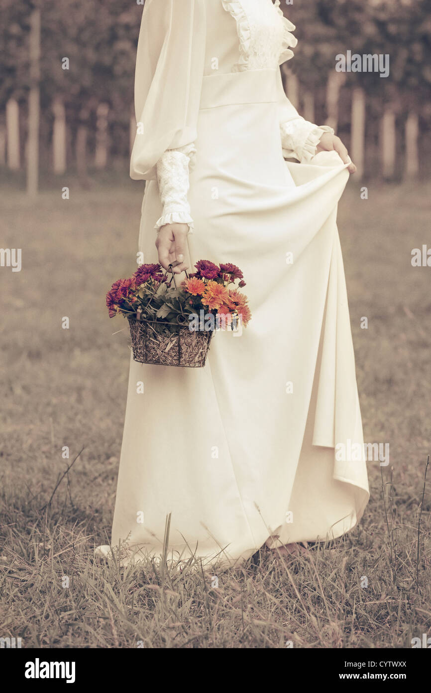 a woman in a victorian dress is walking on a meadow with a basket of flowers - Stock Image