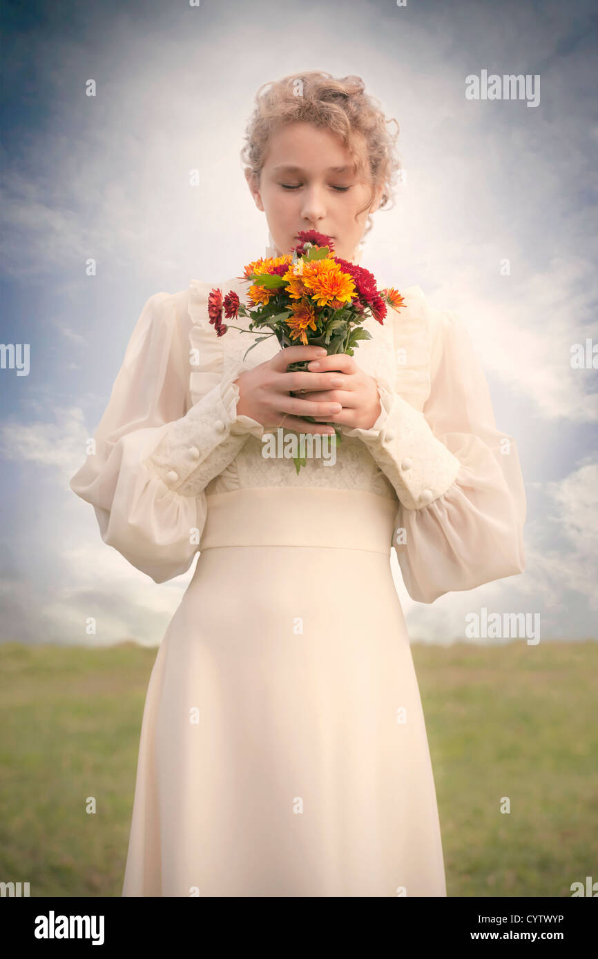 a woman in a victorian dress on a meadow with a bouquet of flowers - Stock Image