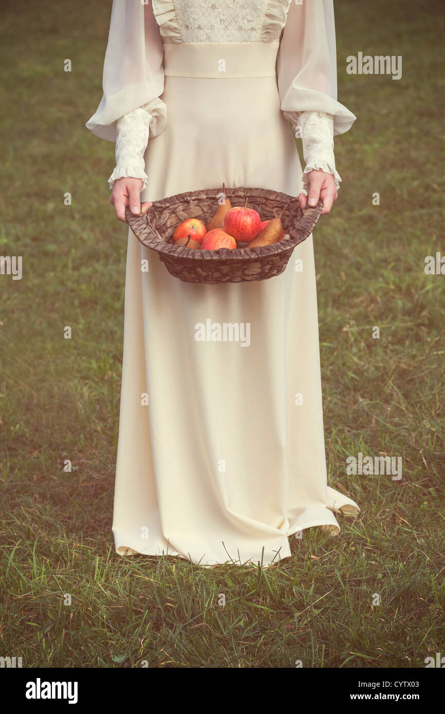 a woman in a white edwardian dress is holding a basket with fruits - Stock Image