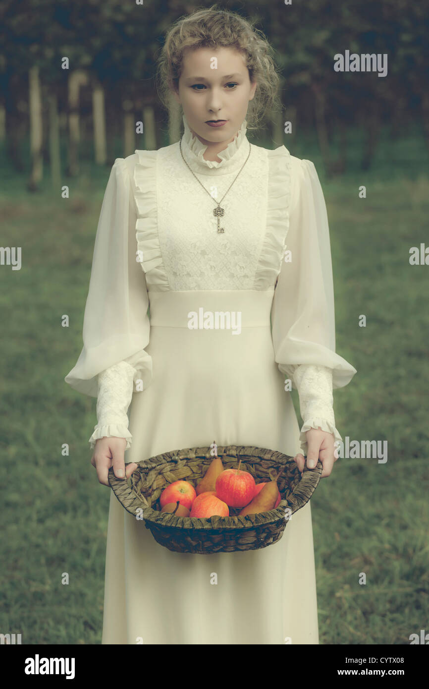 a woman in a white edwardian dress is holding a basket with fruits Stock Photo