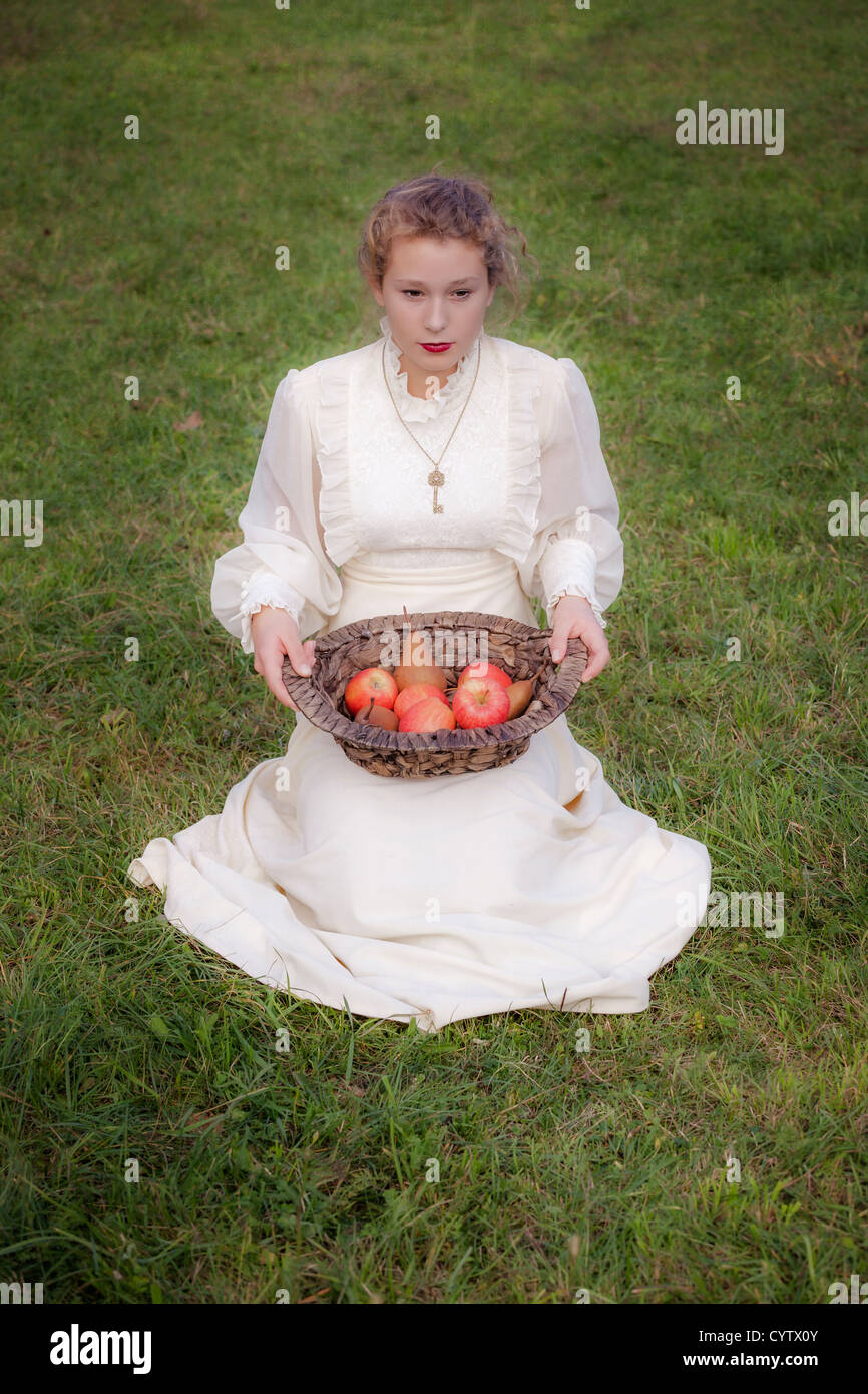 a woman in a white edwardian dress is sitting on a meadow and holding a basket with fruits on her lap - Stock Image