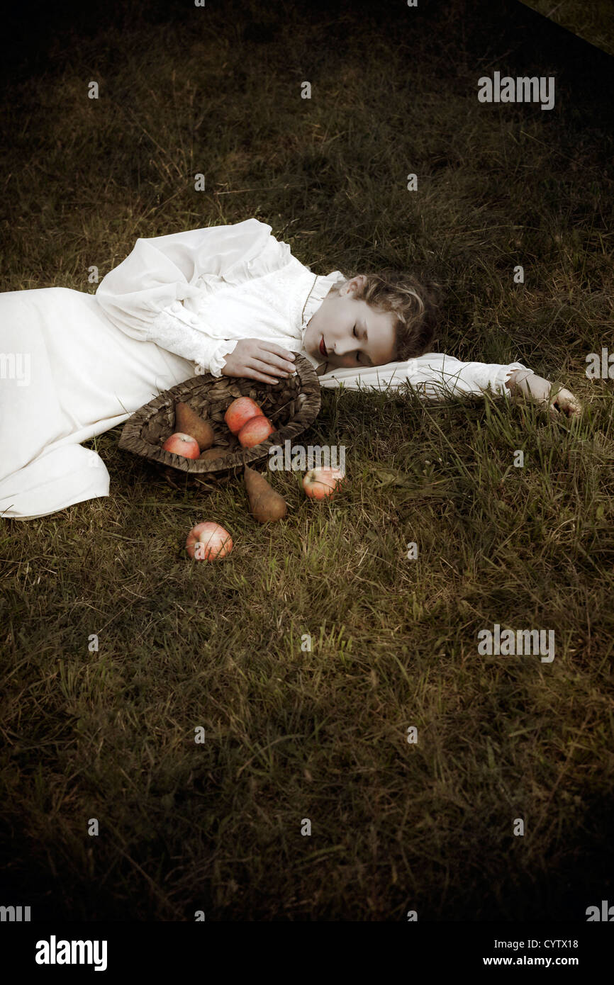 a woman in a white edwardian dress is lying in the grass, in front of her a basket with fruits - Stock Image