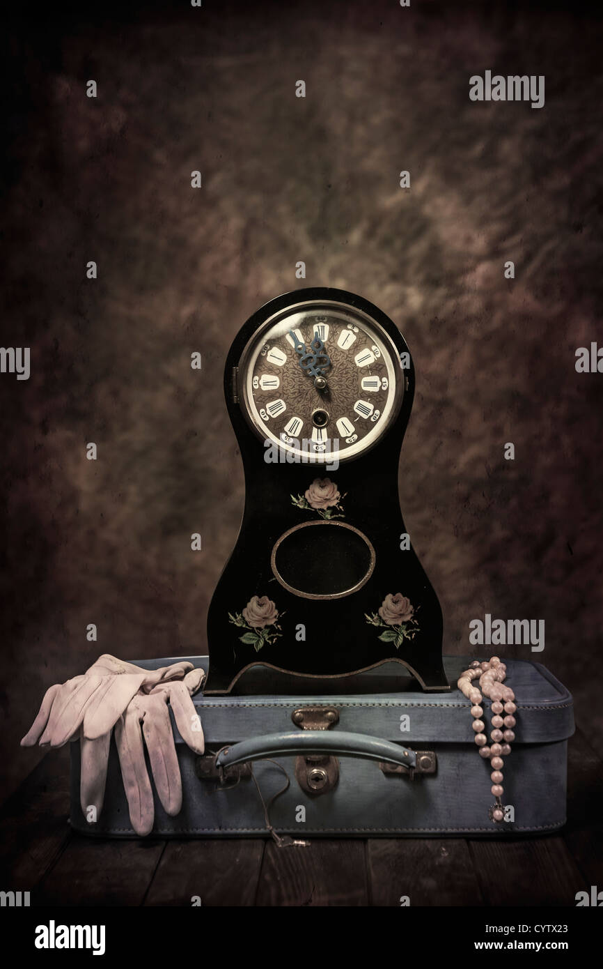 an old table clock in Biedermeier style with a leather suitcase, gloves and a pearl necklace - Stock Image