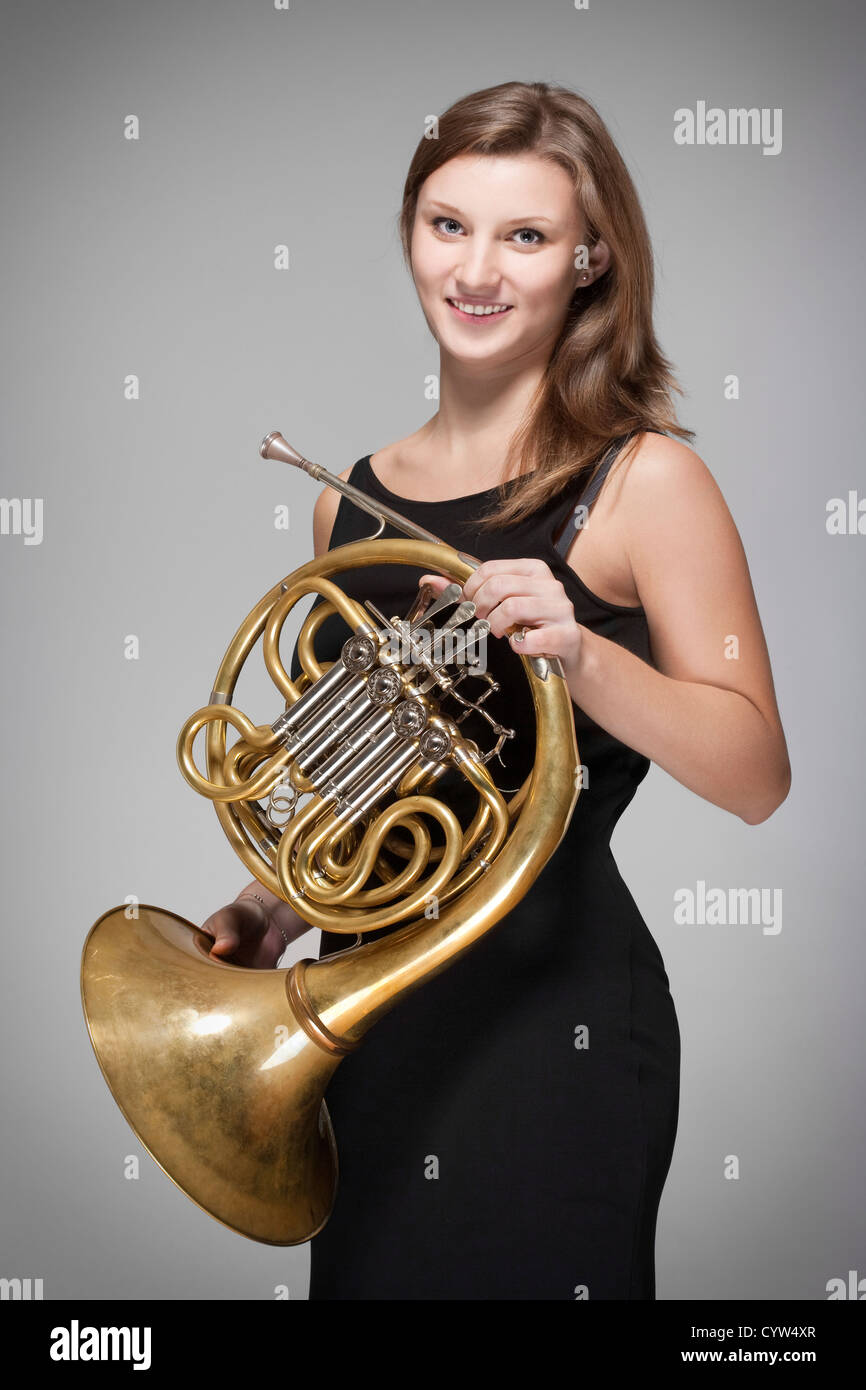 young female musician with concert french horn in black dress - Stock Image