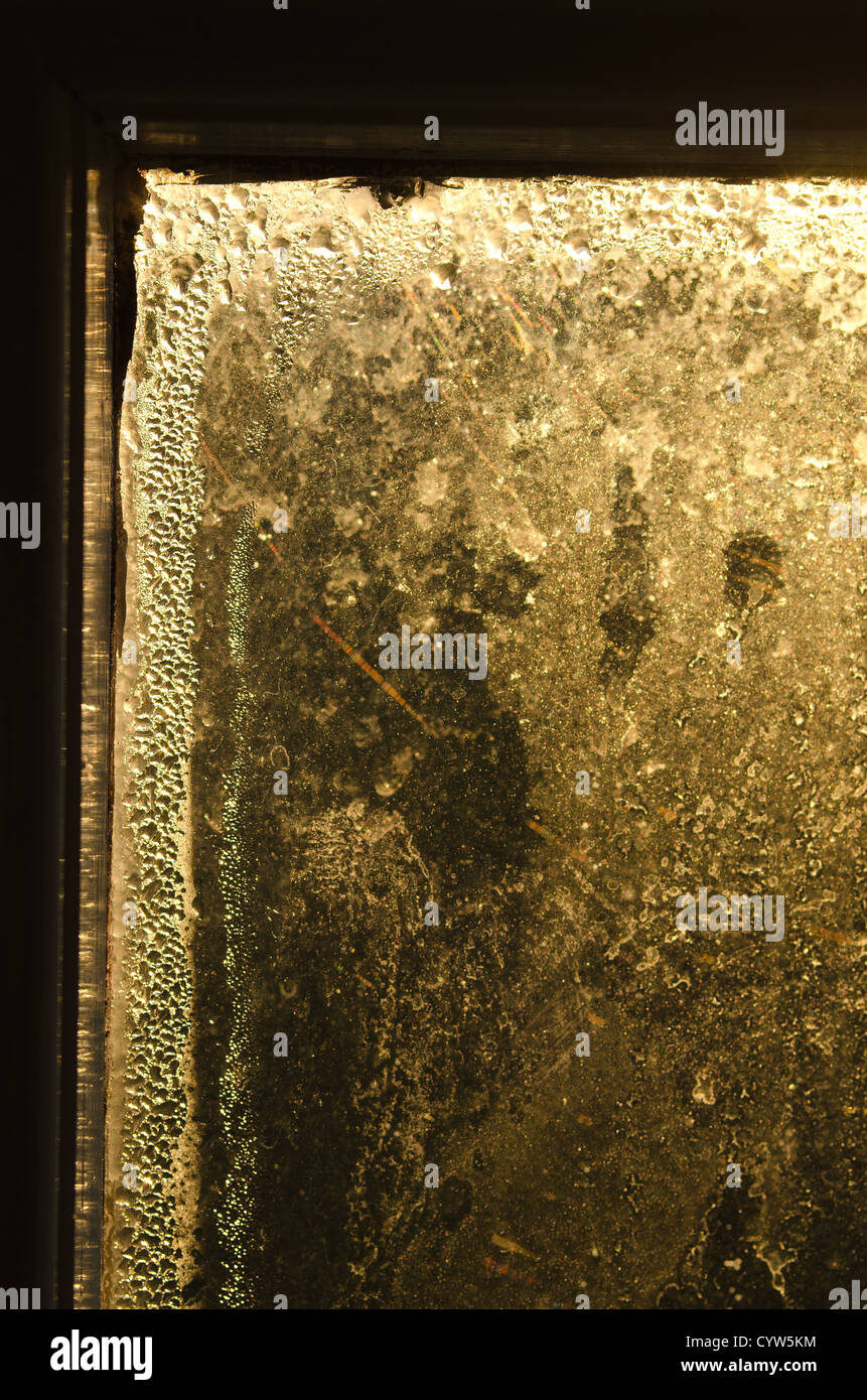 Condensation and obscured vision through glass planes in wooden window frame with sunrise rays of light beaming - Stock Image