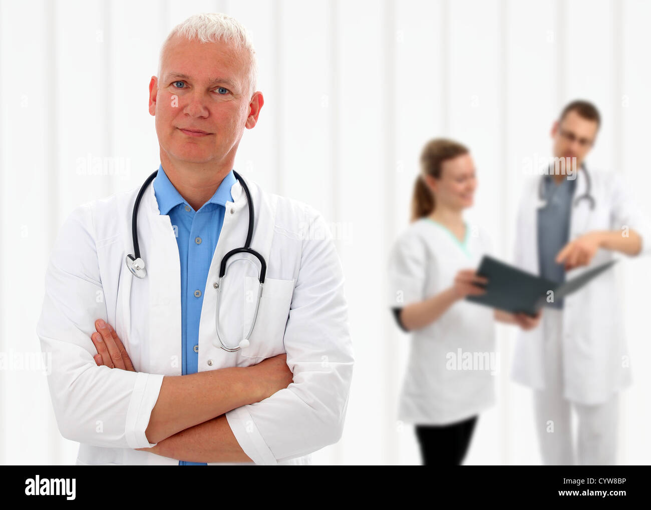 Senior doctor with his arms crossed and a stethoscope around his neck standing in front of his colleagues with shallow - Stock Image
