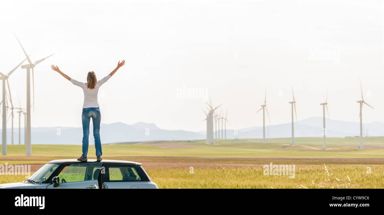 Young woman standing on top of her car with hands raised. Girl in yellow fall field with wind turbines in background. - Stock Image