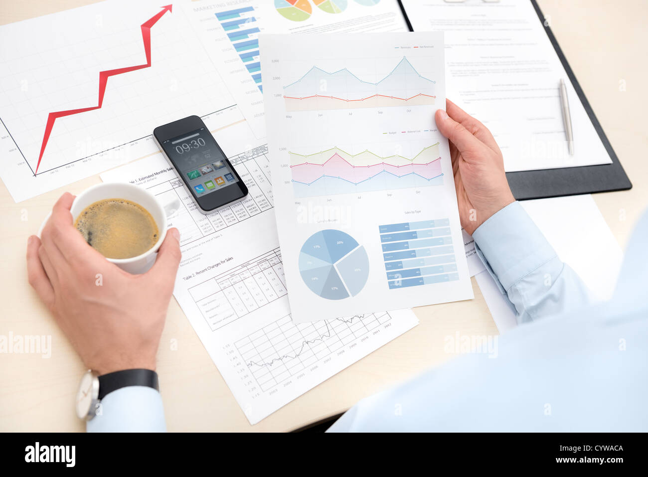 Businessman at the workplace drink coffee and looking some papers with charts and numbers. - Stock Image