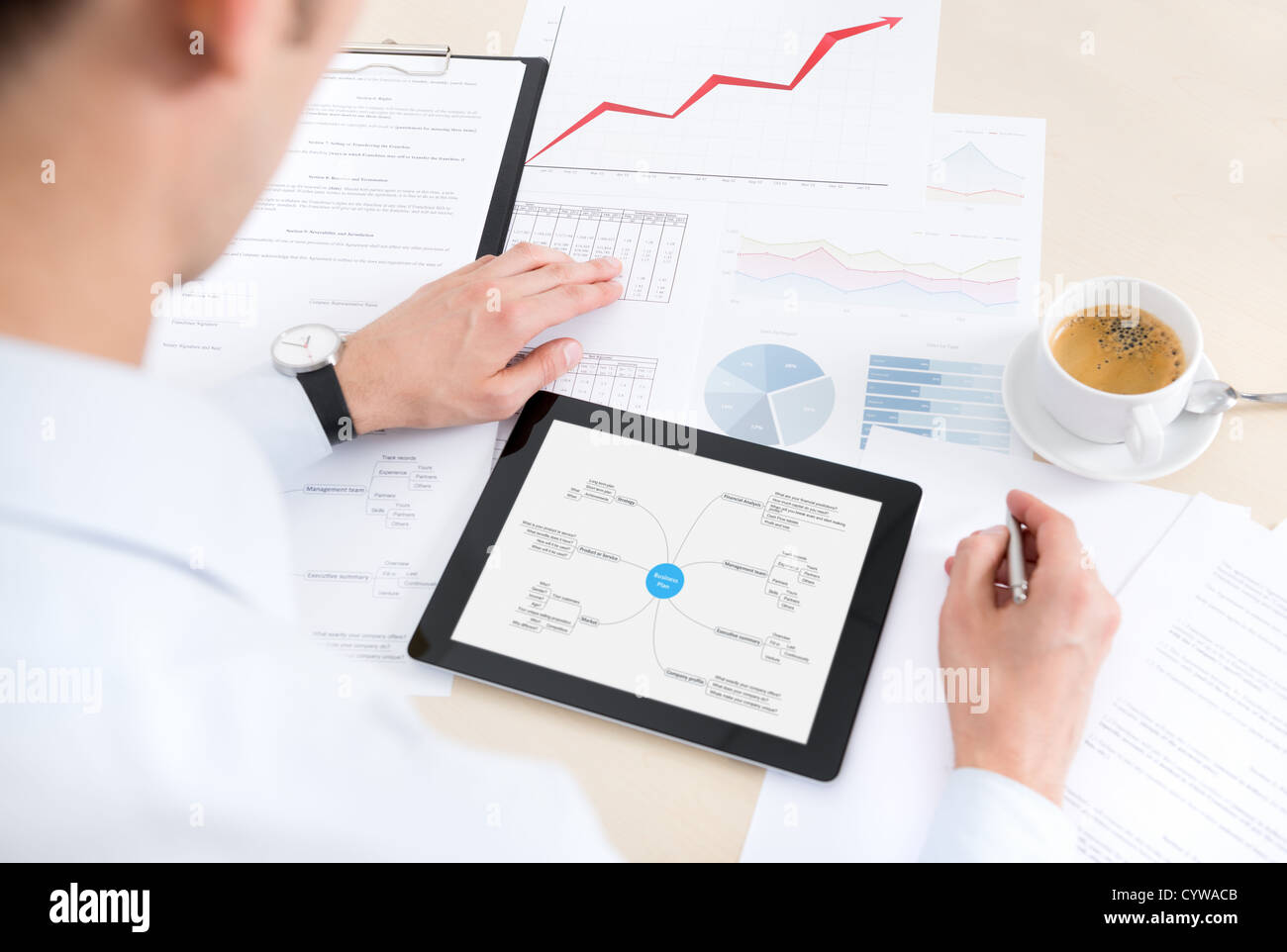 Businessman at the workplace working with documents and using modern digital tablet. - Stock Image