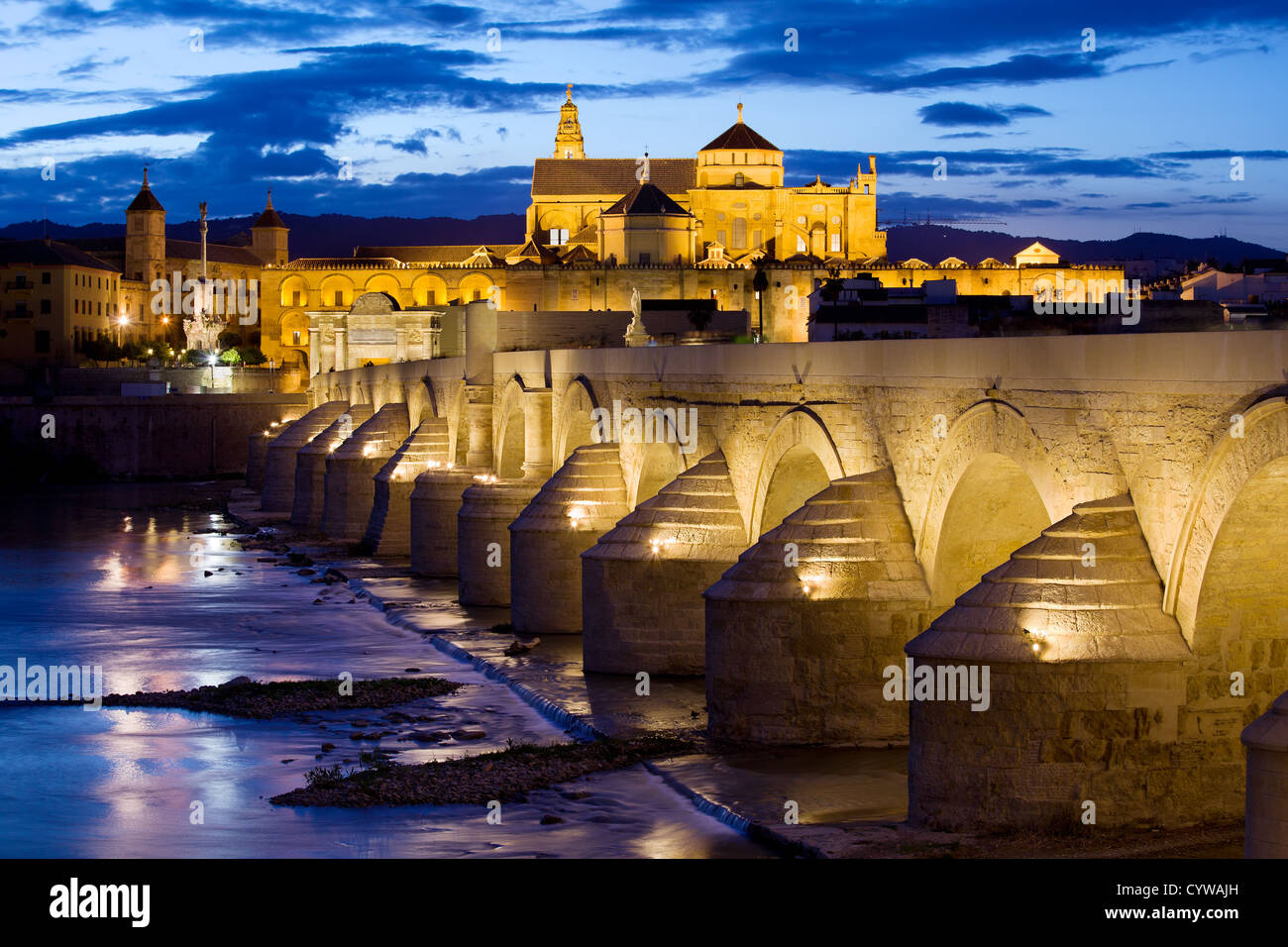 Roman Bridge on Guadalquivir river and Mosque Cathedral (La Mezquita) illuminated at dusk in the city of Cordoba, - Stock Image