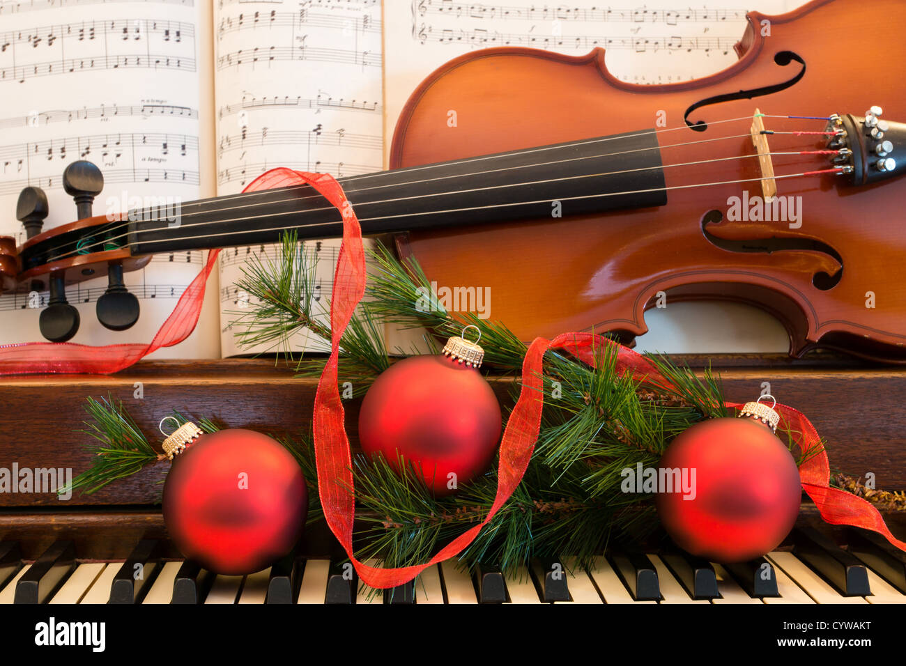 A violin, sheet music, and holiday Christmas decorations sit on an ...