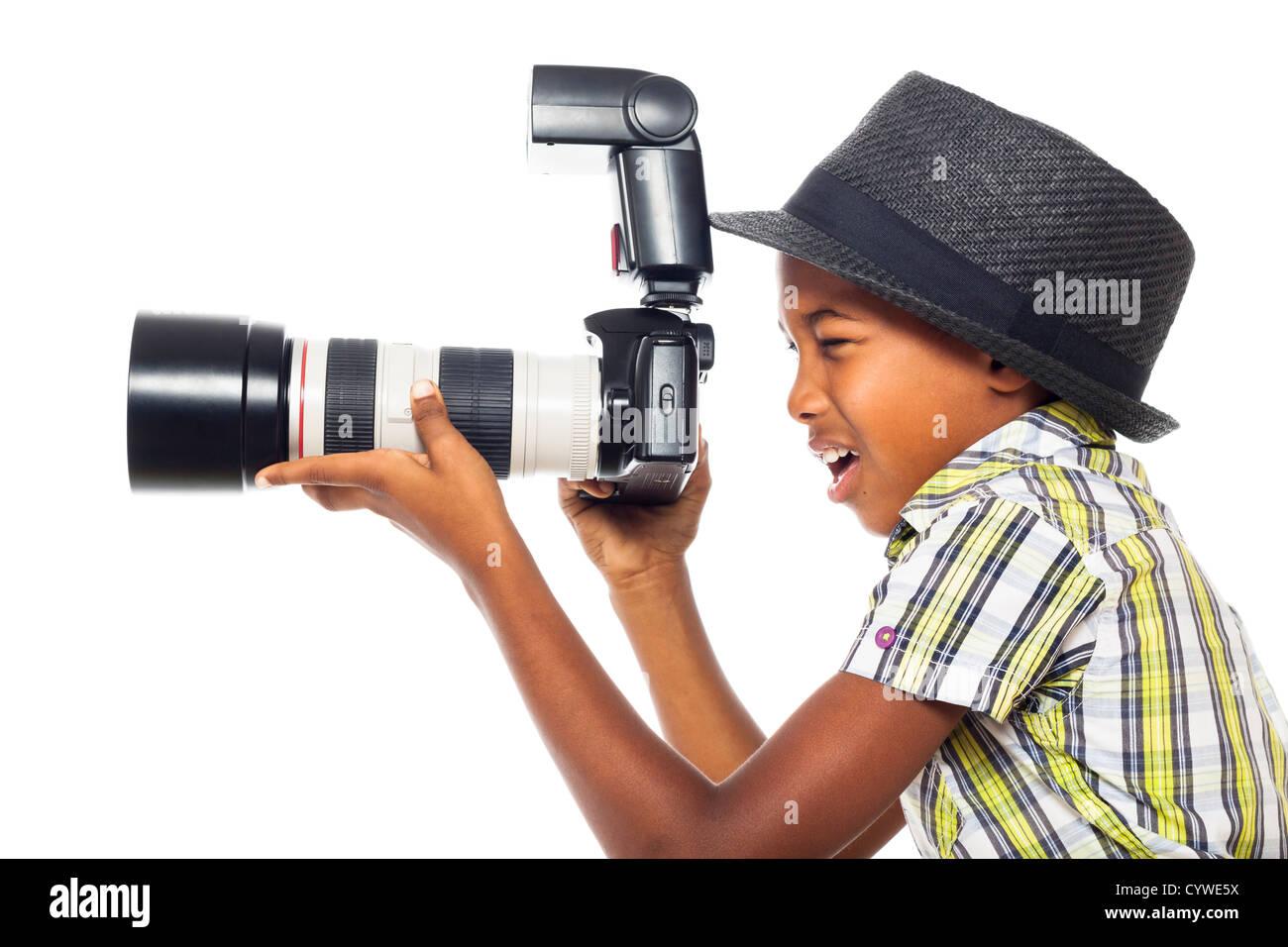 Child boy taking photo with professional camera, isolated on white background. - Stock Image