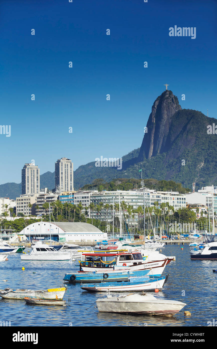 Moored boats in harbour with Christ the Redeemer statue in background, Urca, Rio de Janiero, Brazil Stock Photo