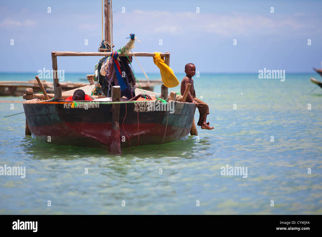 Boy sat on side of fishing boat, Zanzibar, Tanzania. - Stock Image