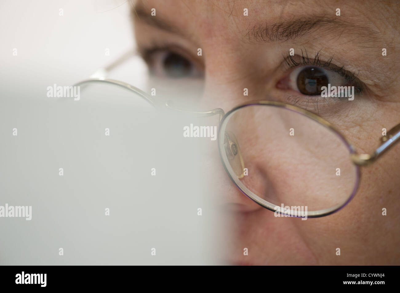 business woman with glasses reading report - Stock Image