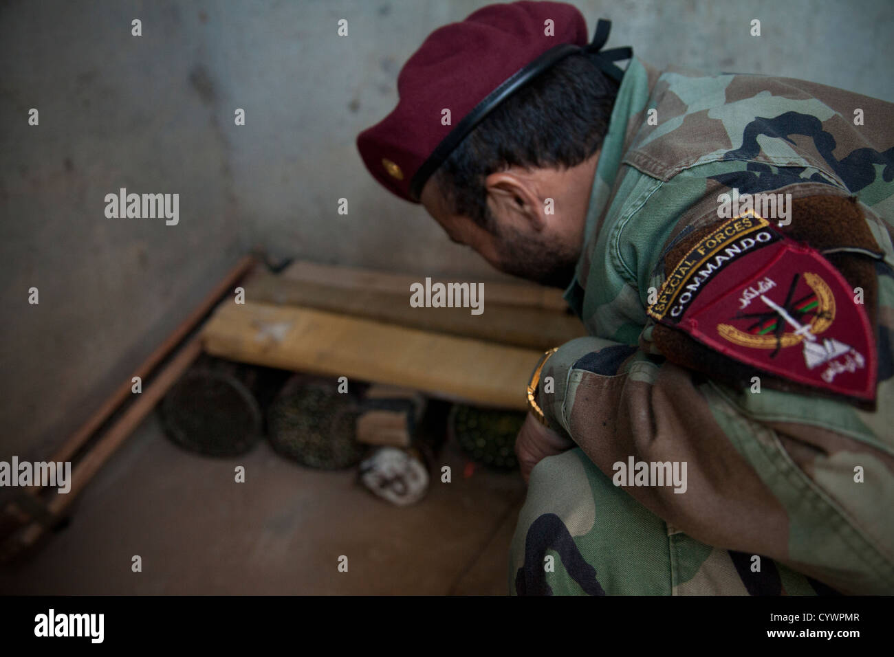 A commando with 9th Special Operations Kandak, Afghan National Army, attempts to recover evidence from a notional - Stock Image