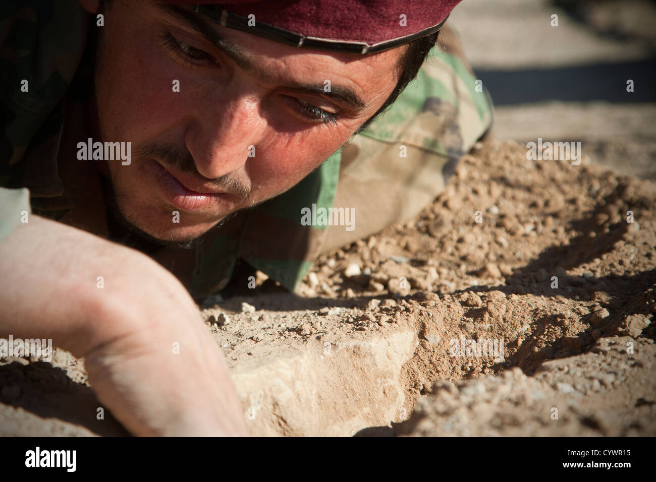 A commando with 9th Special Operations Kandak, Afghan National Army, looks for notional improvised explosive devices - Stock Image