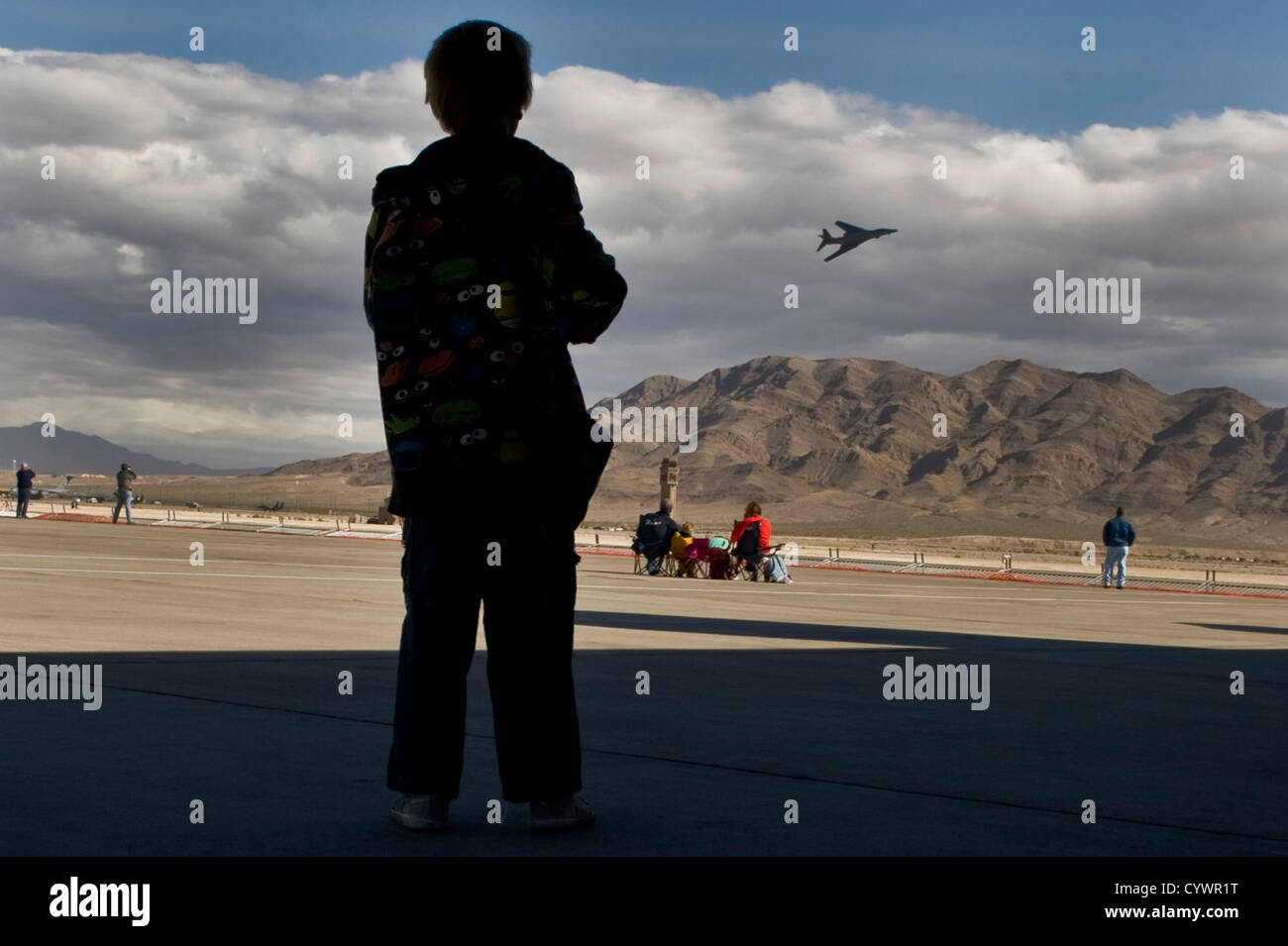 A student from the Innovations International Charter School of Nevada watches as a B-1B Lancer flies at Aviation - Stock Image