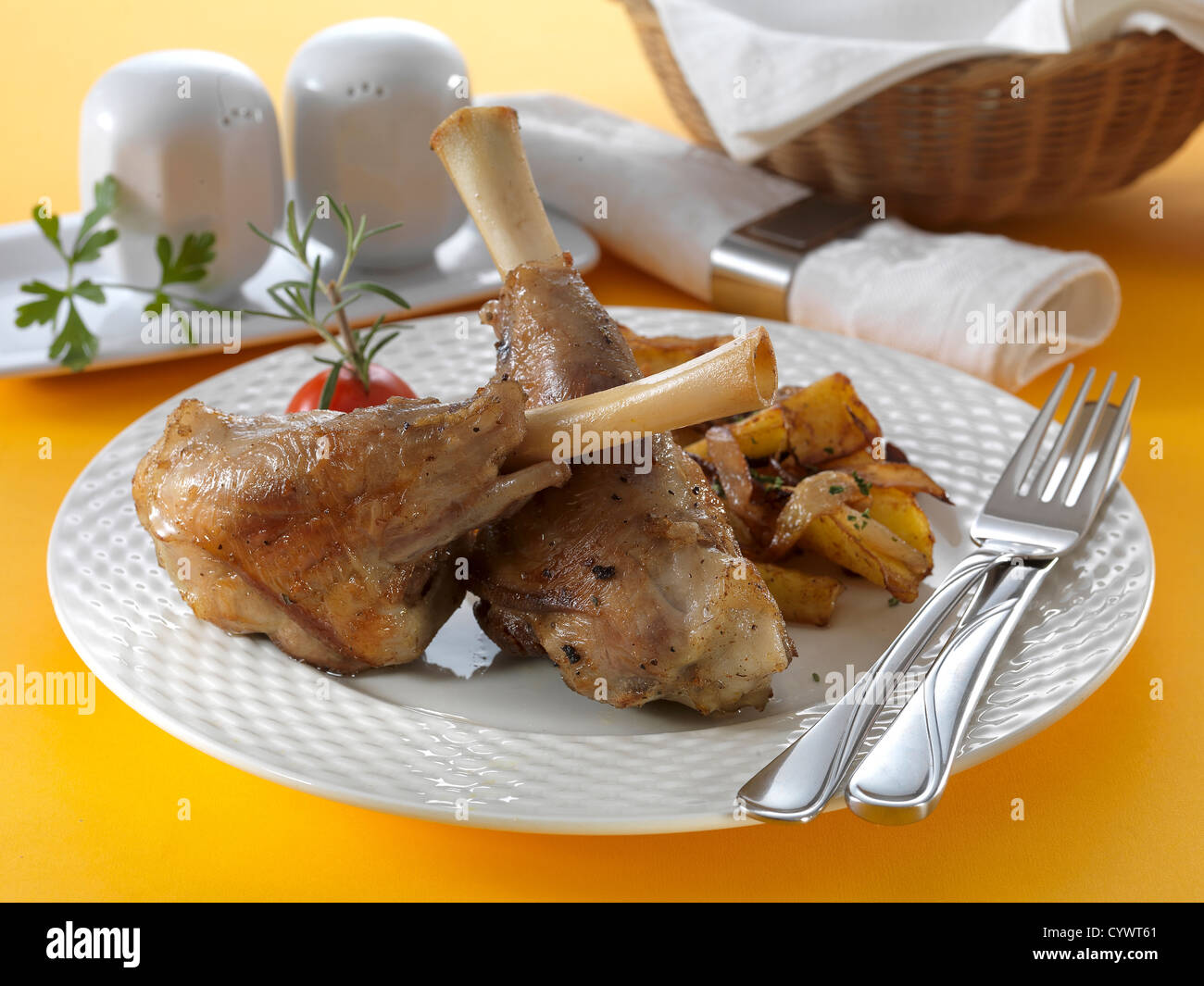 lamb shank Pékné on white plate with chrome fork, knife - Stock Image