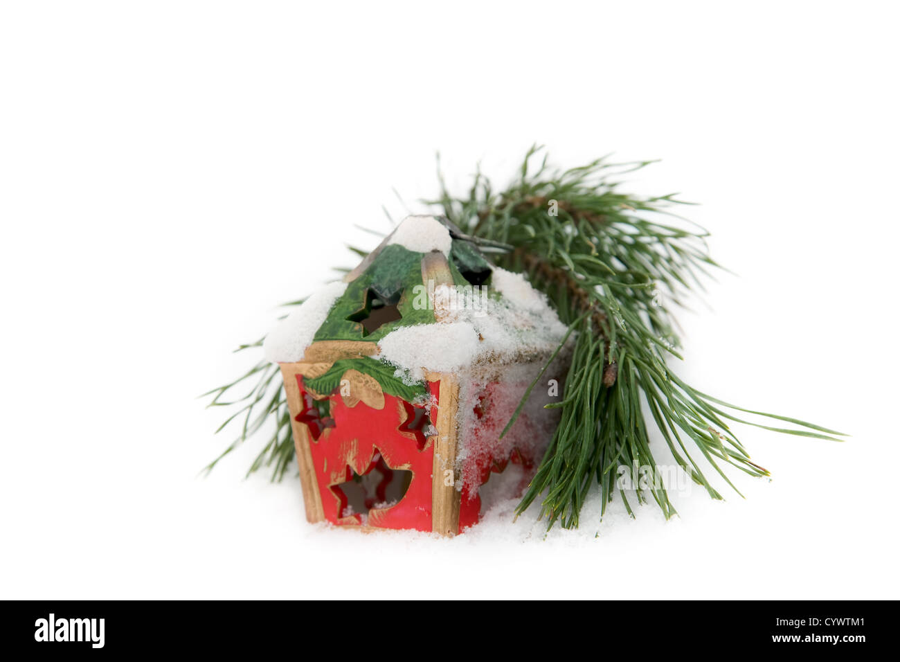 twig of fir and Christmas candle on snow background - Stock Image