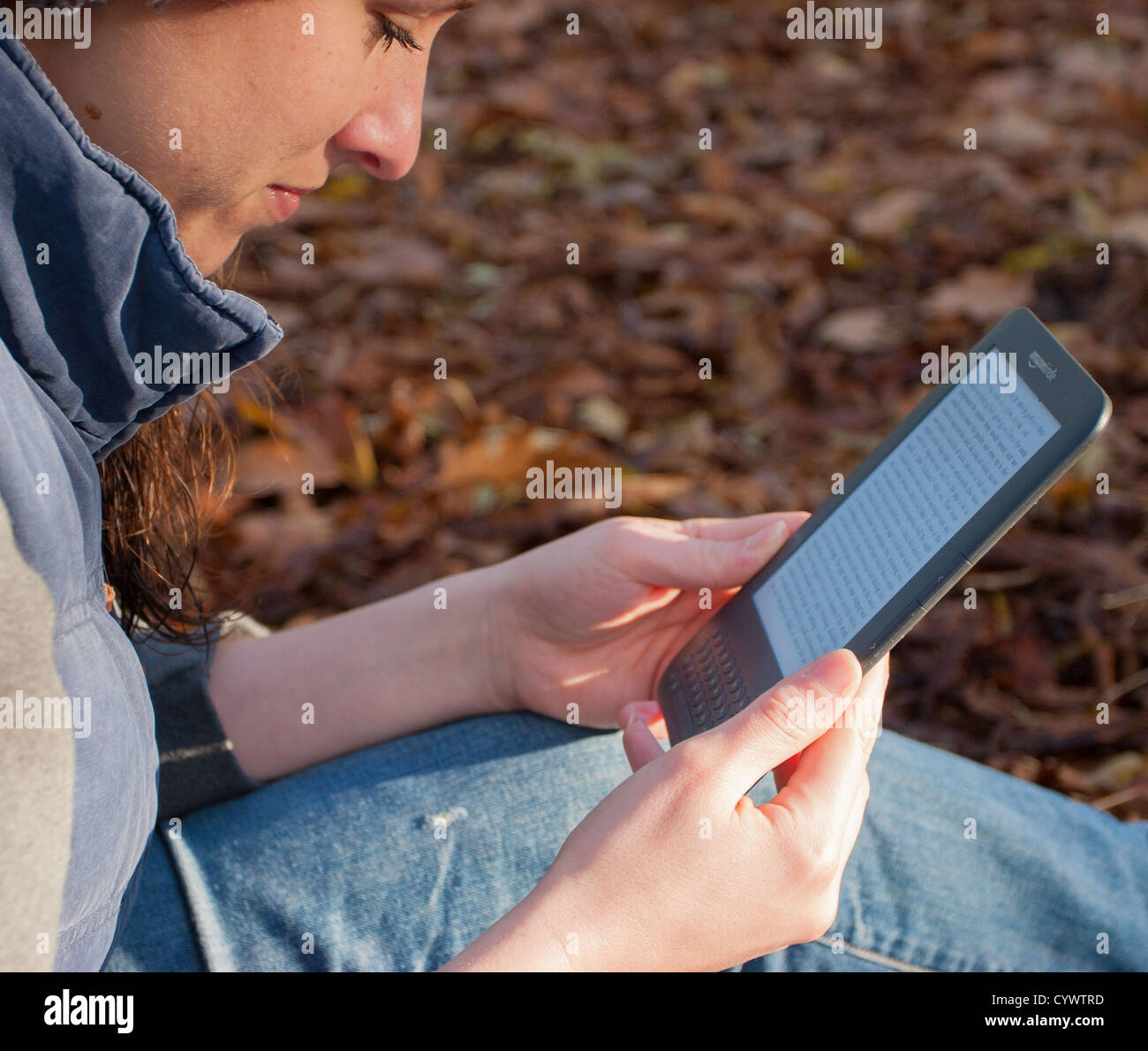 A woman sitting reads an Amazon Kindle ebook reader surrounded by Autumn leaves - Stock Image