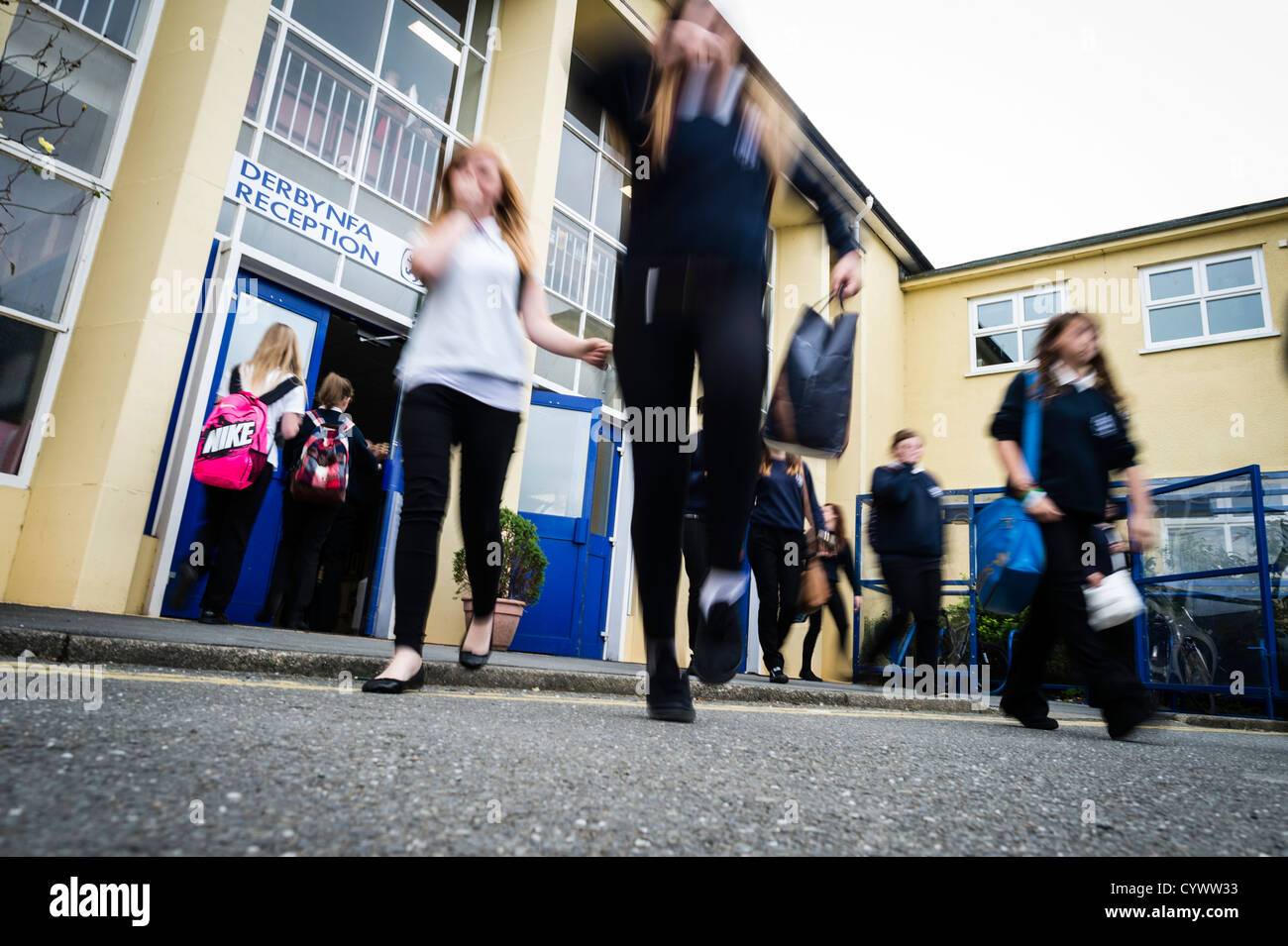 At the end of the day teenage pupils rushing out leaving a secondary school, Wales UK - Stock Image