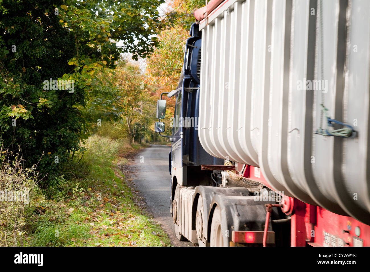 An HGV lorry driving on a narrow country road Suffolk UK - Stock Image